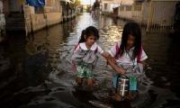 Hai học sinh tiểu học đi bộ qua nước lũ tới trường hồi tháng 10/2018 ở thành phố Mabalacat, tỉnh Pampanga, bờ bắc vịnh Manila. Ảnh: AFP.